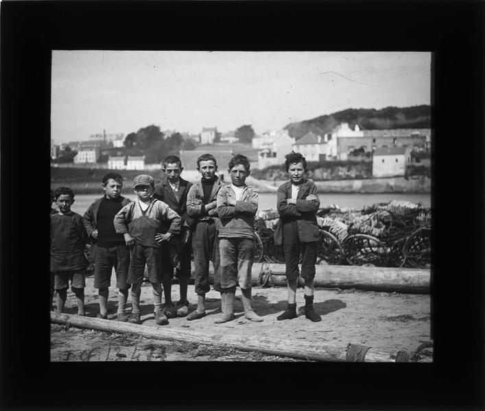 Groupe d'enfants posant sur une plage près de l'entrée du port