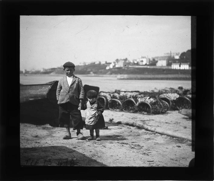 Portrait de deux enfants posant sur une plage près de l'entrée du port
