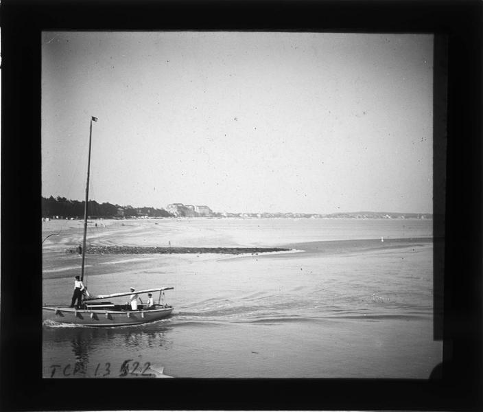 Entrée du port avec bateau et plage de la Baule en arrière-plan