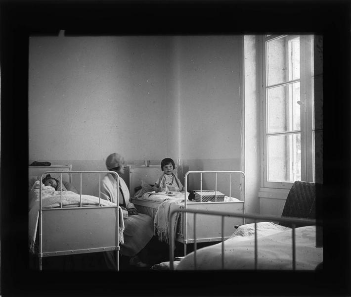 Intérieur : chambre, deux fillettes dans leur lit et femme assise