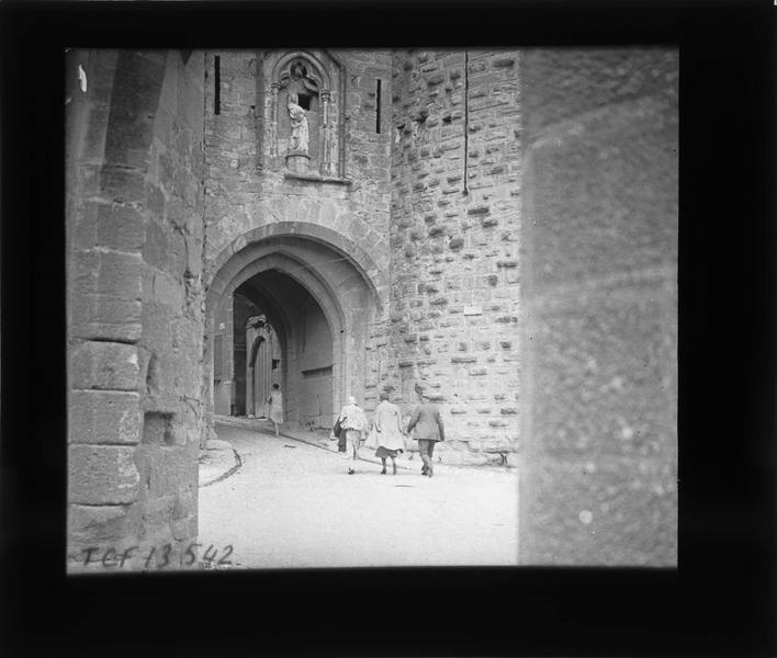 Porte Narbonnaise, arche surmontée d'une statue de la Vierge entre les deux tours et passants