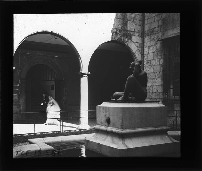 Cour intérieure avec statue de 'La Pensée' d'Aristide Maillot et mariée passant sous les arcades en arrière-plan