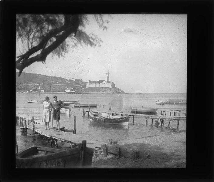 Barques amarrées dans l'anse Cristine, entrée du port et phare en arrière-plan, vue animée