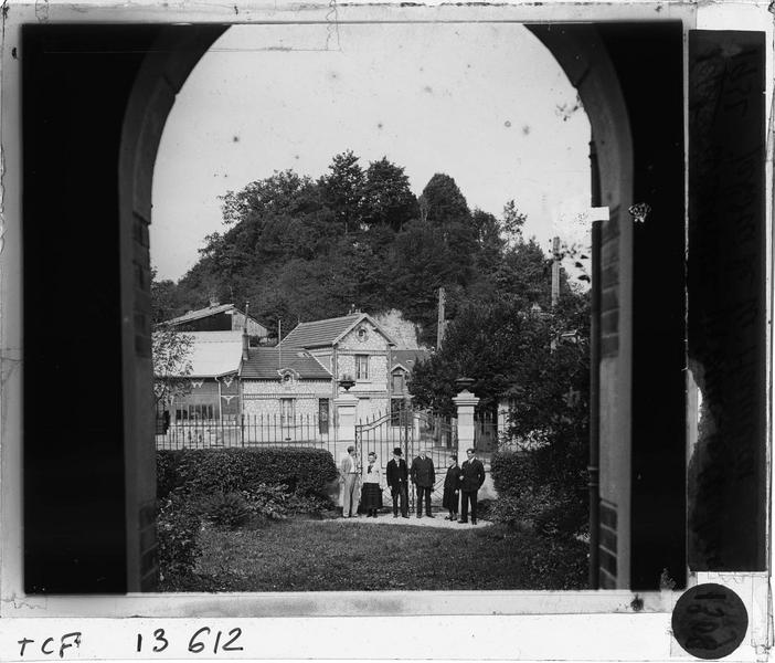 Jardin depuis la fenêtre de la maison et groupe de personnes devant le portail d'entrée (propriété M. Hamelin)