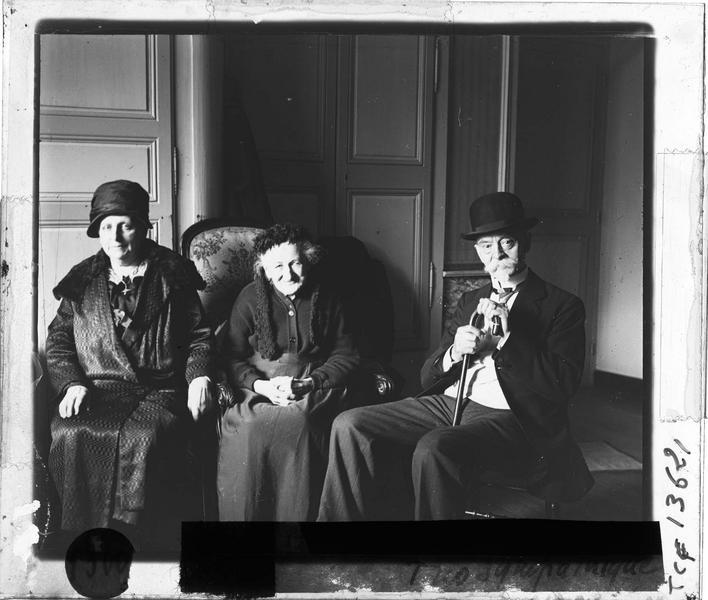 Intérieur : portrait de deux femmes et un homme assis