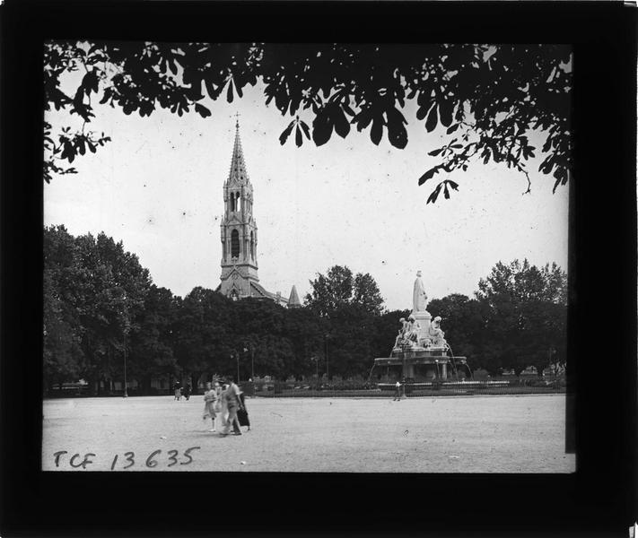 Ensemble sur place animée et clocher de l'église Sainte-Perpétue en arrière-plan