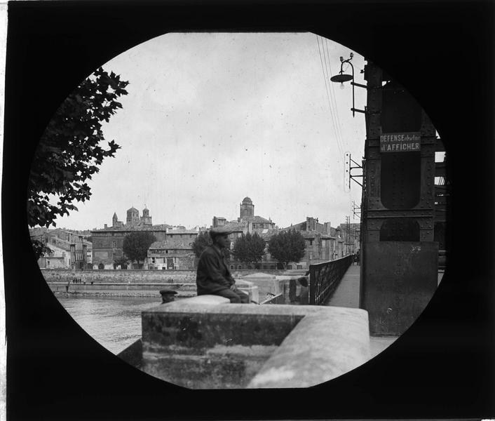 Pont sur le Rhône, vue partielle avec homme assis et ville en arrière-plan