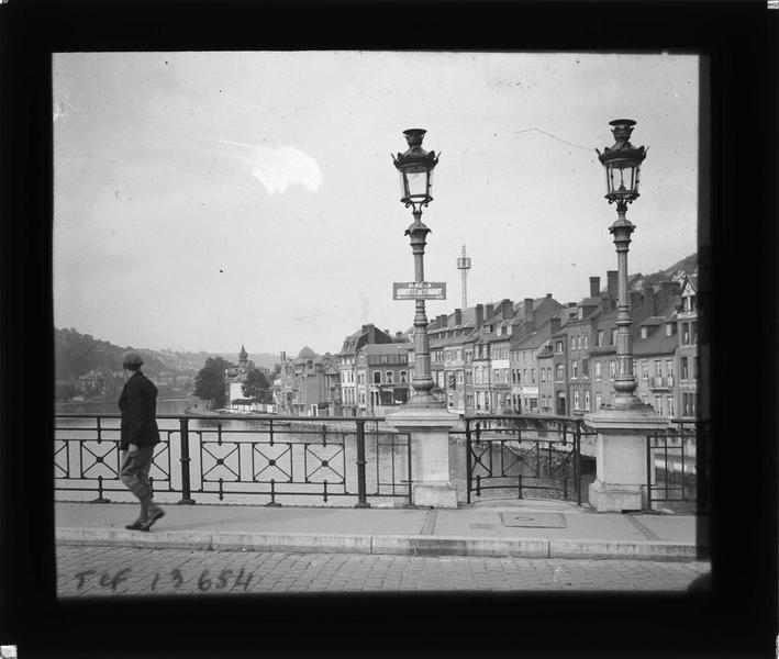 Lampadaires et homme sur le pont et maisons sur la Meuse en arrière-plan