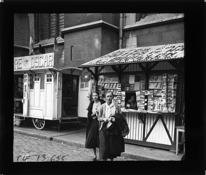 Marchands au pied de la collégiale Notre-Dame et deux femmes