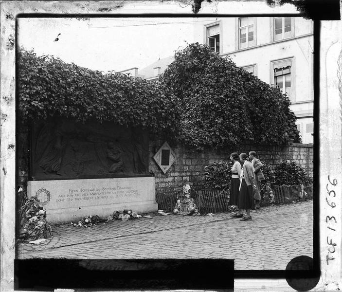 Monument aux morts avec trois personnes devant