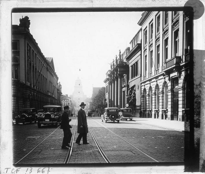 Façades sur rue animée et palais de la Justice en arrière-plan