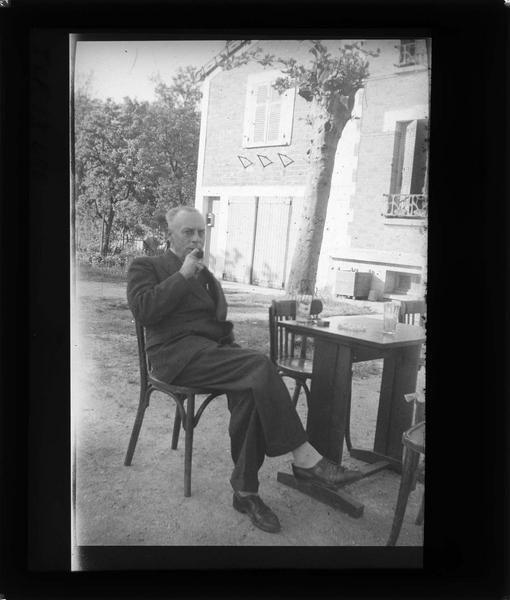Portrait d'un homme fumant assis dans un jardin