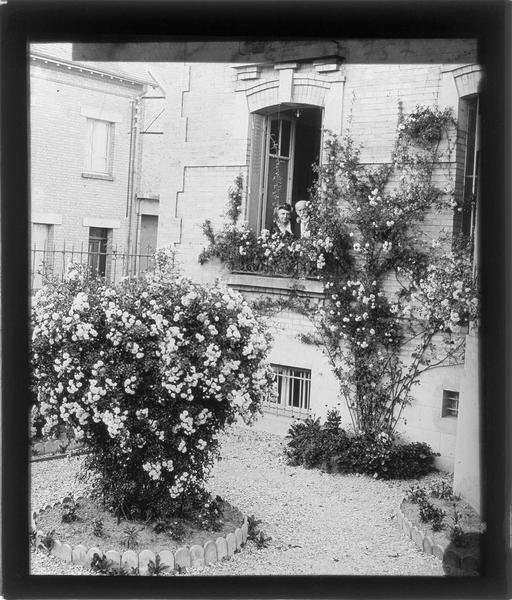 Façade sur jardin avec rosiers, vue partielle et deux personnes à la fenêtre