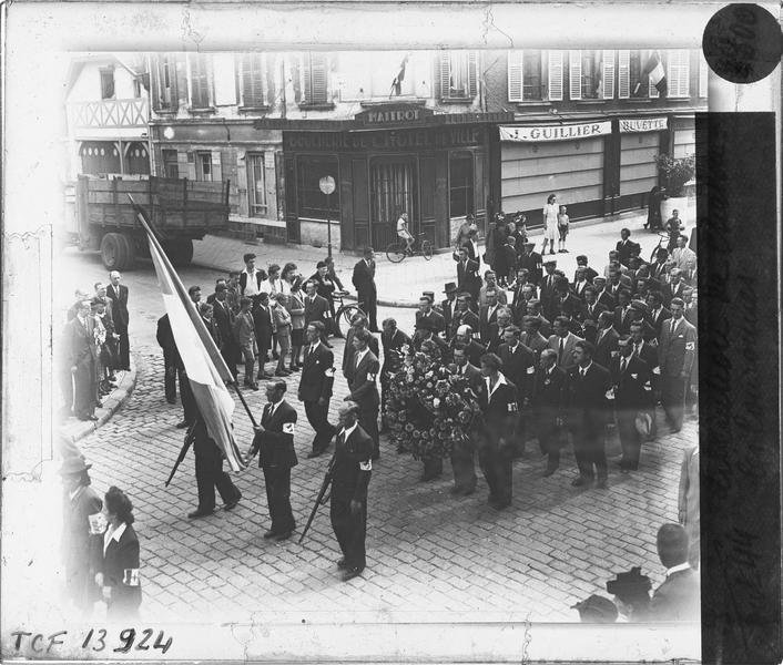 Défilé de la Libération : porte-drapeau suivi d'un cortège d'hommes avec brassards et couronne de fleur