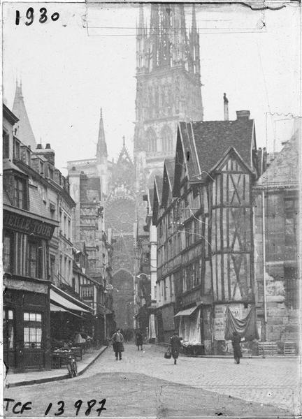 Façades sur rue animée, transept sud et flèche de la cathédrale en arrière-plan