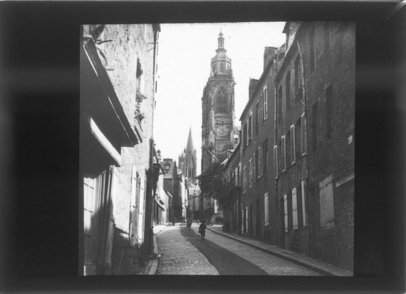 Façades sur rue et clocher de l'église Saint-Pierre en arrière-plan