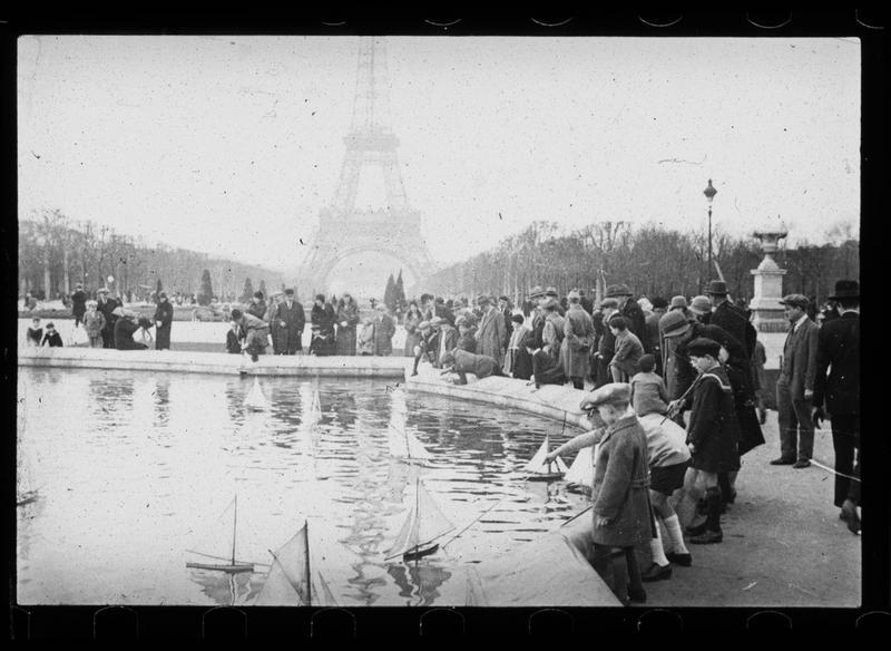Bassin, vue animée avec enfants jouant avec des bateaux à voiles et Tour Eiffel en arrière-plan
