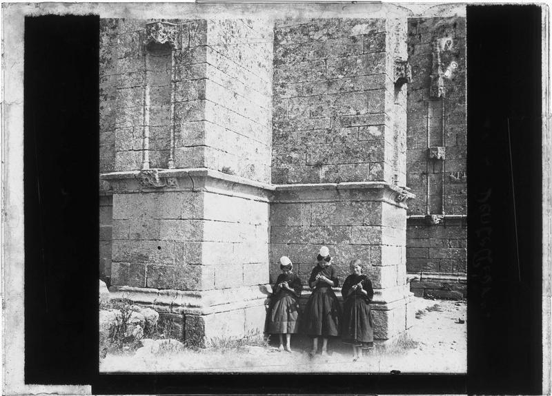 Trois jeunes dentellières adossées contre le mur d'une église