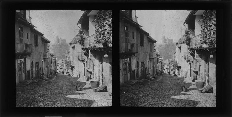 Façades sur rue animée et château en arrière-plan