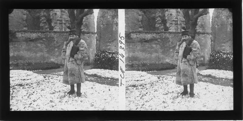 Homme en fourrure dans un jardin enneigé