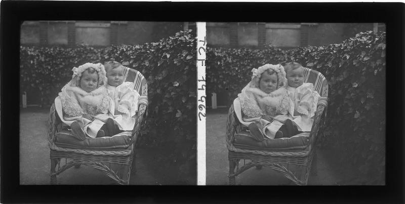 Portrait de deux enfants assis sur un fauteuil dans un jardin