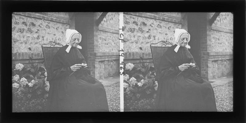 Portrait d'une vieille femme tricotant assise dans un jardin
