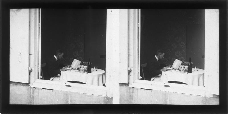 Intérieur : portrait d'un homme attablé vu depuis une fenêtre