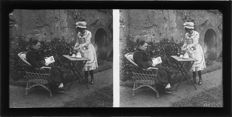Portrait d'une domestique servant le thé à une femme assise dans un jardin