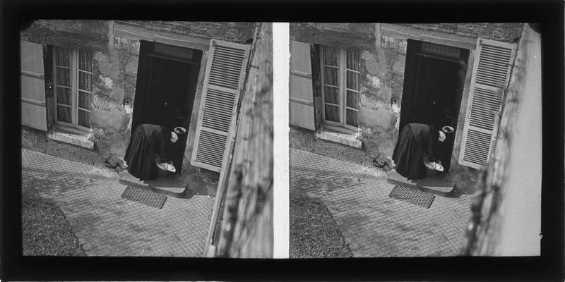 Femme à la porte d'une maison fouillant un panier, vue en plongée