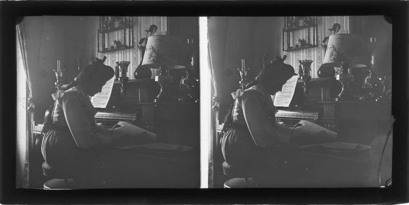 Intérieur : portrait d'une femme lisant une partition assise à côté d'un piano