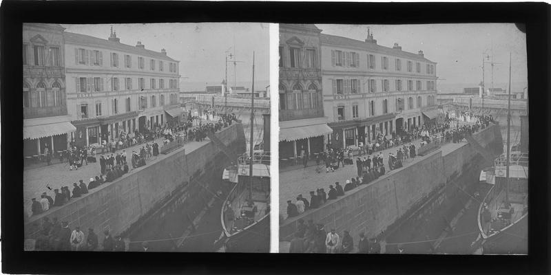 Façade sur quai animée avec procession religieuse lors de la fête du couronnement de Notre-Dame de Grâce le 19 juin