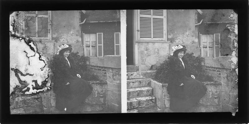 Portrait d'une femme portant un manteau de fourrure et un chapeau assise devant une maison