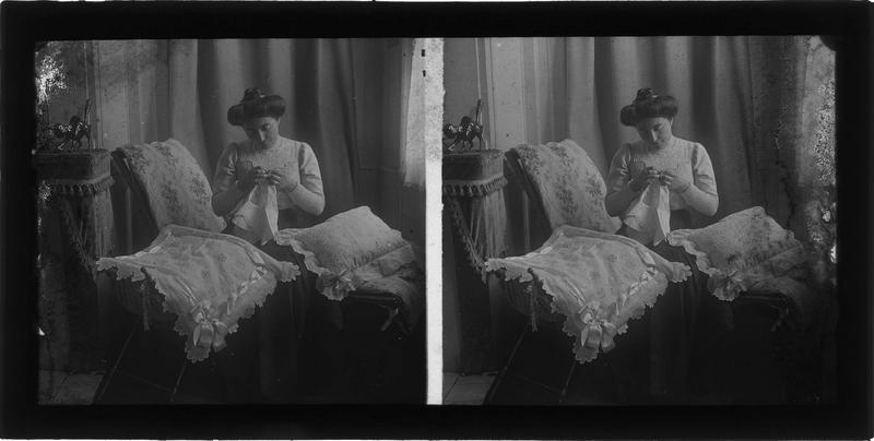 Intérieur : portrait d'une femme cousant assise dans un salon entourée de coussins brodés
