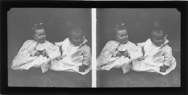 Intérieur : portrait de deux bébés assis sur un tapis