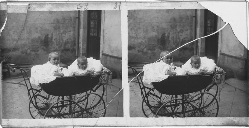Portrait de deux bébés assis dans un landau dans une cour