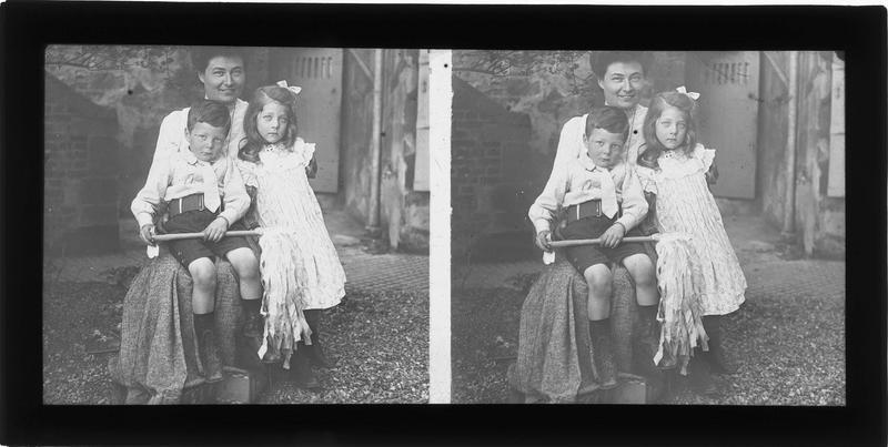 Portrait d'une femme et de deux enfants dans une cour