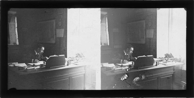 Intérieur : portrait d'un homme écrivant assis derrière un bureau sur lequel se trouvent un châssis-presse et des vues stéréoscopiques
