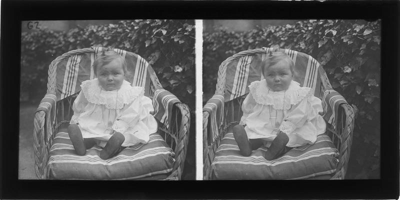 Portrait d'un bébé assis sur une chaise en osier