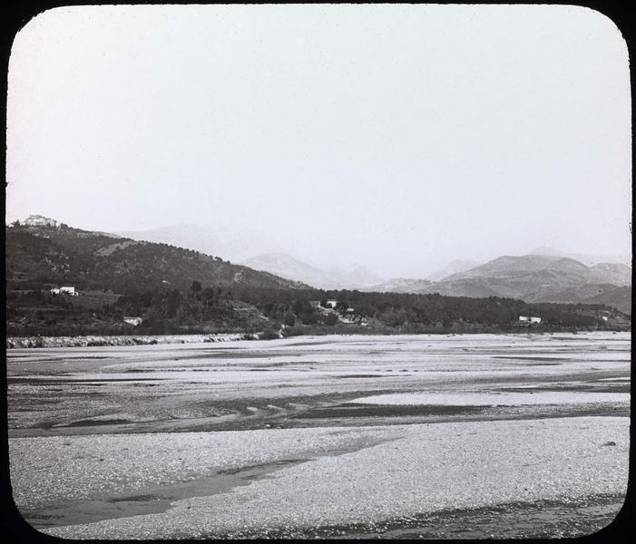 Lit d'un fleuve asséché (?) et montagnes en arrière-plan