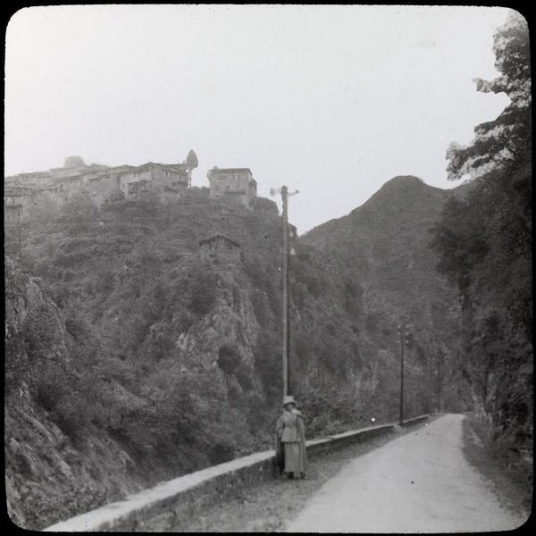 Maisons sur éperon rocheux depuis la route (M2565) et femme au premier plan