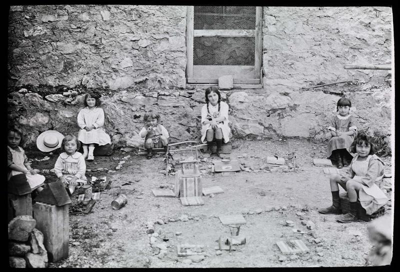 Groupe d'enfants assis dans une cour avec des jouets
