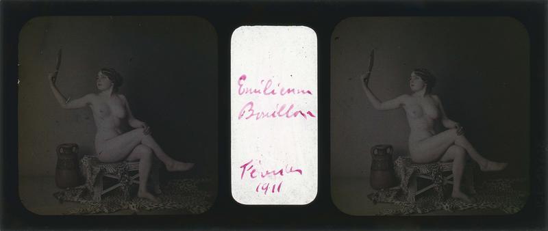 Emilienne Bouillon posant nue, assise jambes croisées et miroir à la main, dans un décor avec jarre et peau de panthère