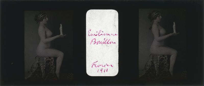 Emilienne Bouillon posant nue, assise de profil sur une peau de panthère une statuette dans la main