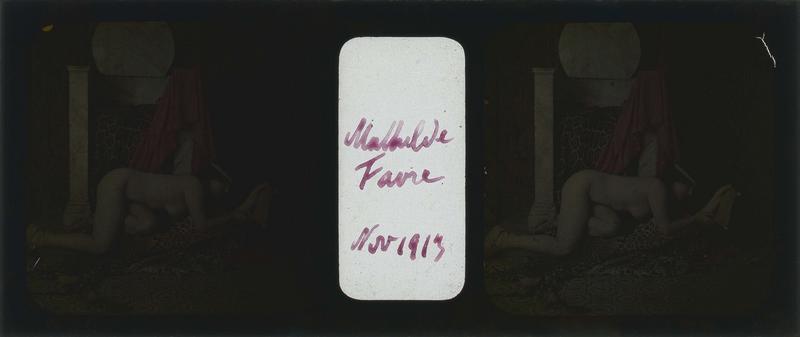 Mathilde Favre posant nue, couchée sur une peau de panthère, lisant un rouleau au pied d'un siège en marbre