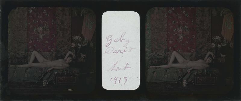 Gaby David posant nue, couchée sur un canapé, dans un décor japonisant avec étoffes, théière et statuettes