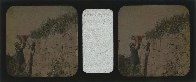 Homme aidant une femme à passer au-dessus d'un muret en pierre