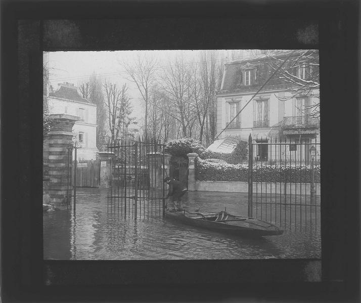 Crue de la Seine : façade sur rue inondée et homme sur une barque au premier plan