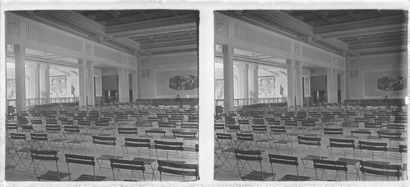 Intérieur : salle remplie de chaises pliantes; peinture de Barat-Levrault intitulée 'L'lndustrie'