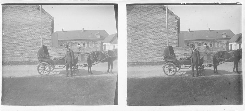 Homme posant à côté d'un enfant allongé dans une voiture à cheval devant une maison
