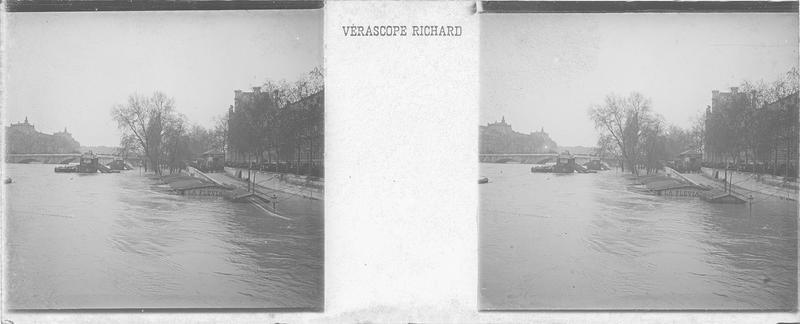 Crue de la Seine : embarcadères et quai inondés depuis le pont du Carroussel animé, et pont Royal en arrière-plan
